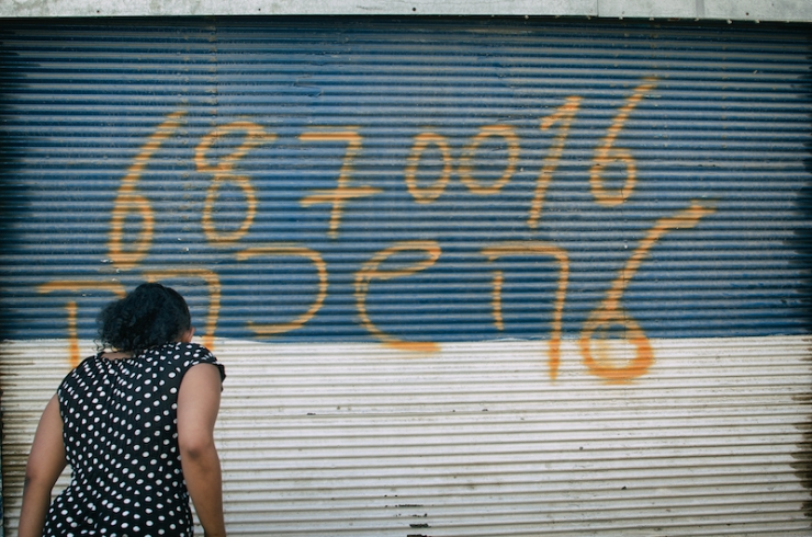 Een Eritrese voor haar computerwinkel die is leeggeroofd. Foto: Alfred Muller