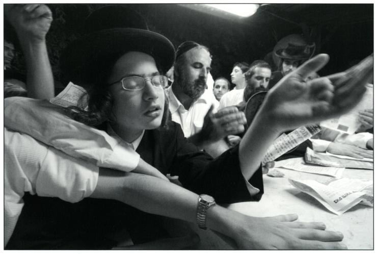 1 Een chassidische jongen bidt vol overgave bij het graf van de tzadiek van Shtefanesht, rabbijn Avraham Mattisyahu Friedman. Tel Aviv, 2006. De tzadiek stierf in 1933. Zijn stoffelijke overschot werd in 1969 naar Israël gebracht. Foto: Yuval Nadel, Israël Museum.