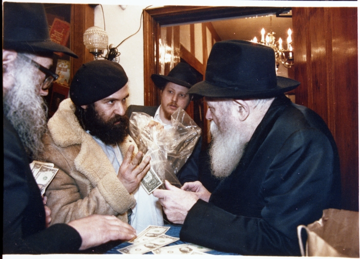 De Lubavitcher Rebbe geeft dollars aan Avrahaum G. Segol in Brooklyn, New York, 1988. Foto: privé collectie Avrahaum G. Segol