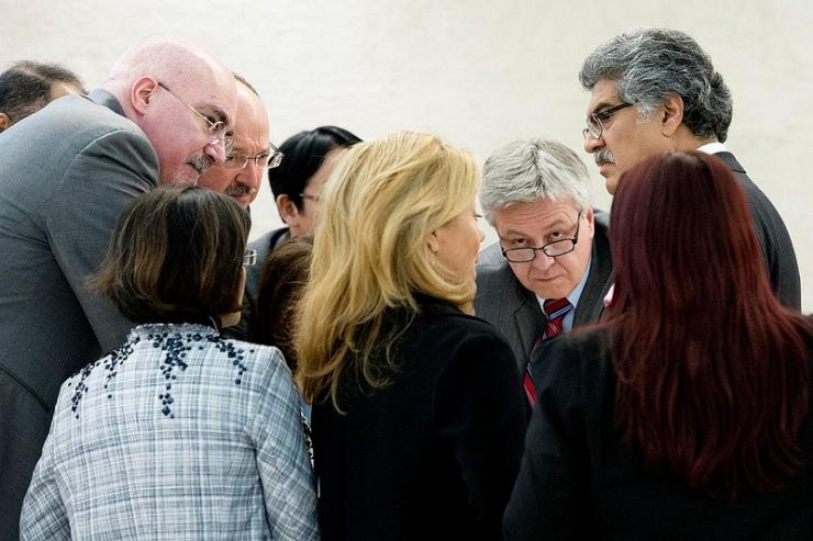 De president van de VN Mensenrechtenraad, de Poolse vertegenwoordiger Remigiusz A. Henczel (gezicht naar de camera) in gesprek met delegatieleden tijdens de Universele Periodieke Doorlichting. Foto: VN, Jean-Marc Ferré.