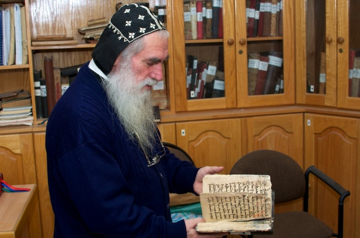 Pater Shemun in de biblitheek van de kerk, met eeuwenoude Aramese documenten. Foto: © Alfred Muller