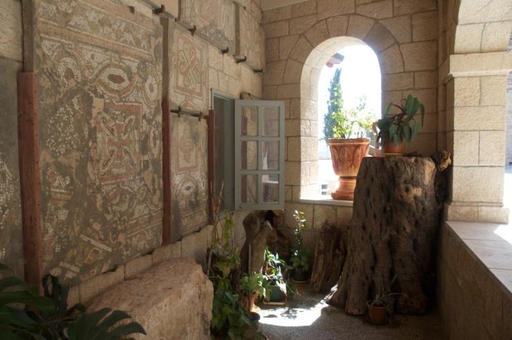Het mozaïek met een rood kruis op de muur van de Stefanuskerk in Bet Gemal. Het mozaïek bevond zich oorspronkelijk in een Byzantijnse kerk op dezelfde plaats.  Foto's: © Alfred Muller