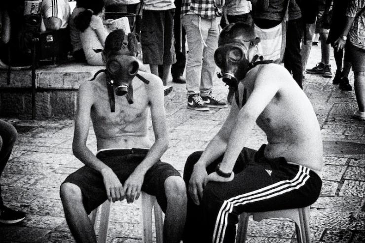 Twee jongens in de binnenstad van Jeruzalem hebben bij een ludieke actie oude gasmaskers opgezet. Foto: © Alfred Muller