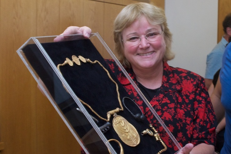 Dr. Eilat Mazar toont de medaille met de afbeelding van een menora, sjofar en torarol en andere zilveren en gouden voorwerpen. Foto: © Alfred Muller