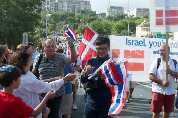 Een deelnemer uit Thailand deelt vlaggetjes uit aan Israëli's tijdens de Jeruzalemmars. Foto: © Alfred Muller