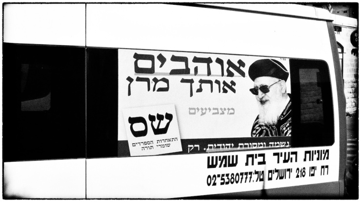 Een poster van de Shas partij en rabbijn Ovadia Yosef op een taxi. Foto: Alfred Muller