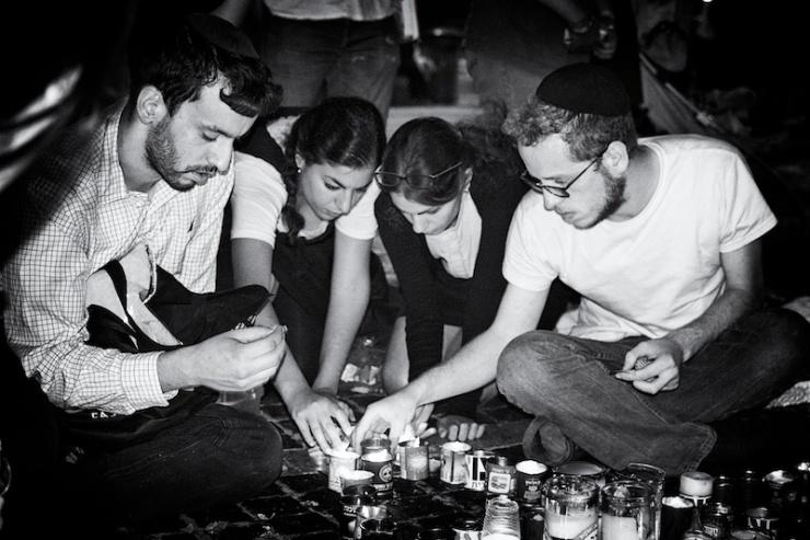 Jonge Israëliërs branden kaarsen voor de drie vermoorde leeftijdsgenoten. Foto: © Alfred Muller