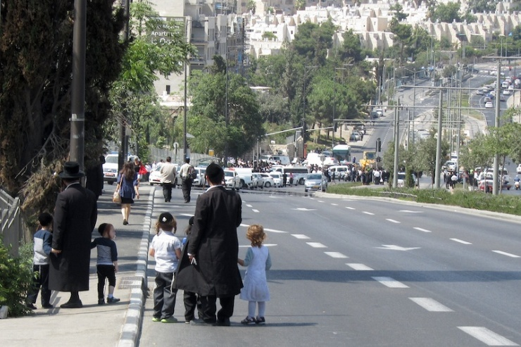 Ultraorthodoxe vaders en hun kinderen kijken in de richting waar de aanslag plaatsvond.  Foto: © Alfred Muller