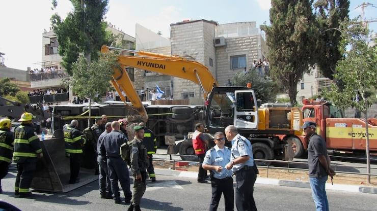 Politieagenten en brandweerlieden bij de sjofel en de omver geworpen bus. Foto: © Alfred Muller.