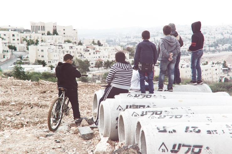 Palestijnse jongens in de Arabische wijk Shuafat in Jeruzalem kijken naar de Joodse wijk Ramat Shlomo. Foto: © Alfred Muller