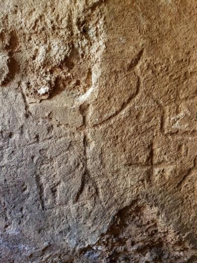 Afbeeldingen van menselijke figuren en kruisen in een muur. Foto: Gilad Itach, IAA